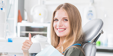 A woman sitting on dentist chair giving thumbs up