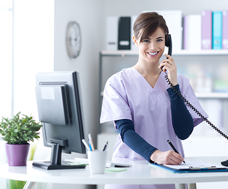 A dental office receptionist talking to a patient on phone