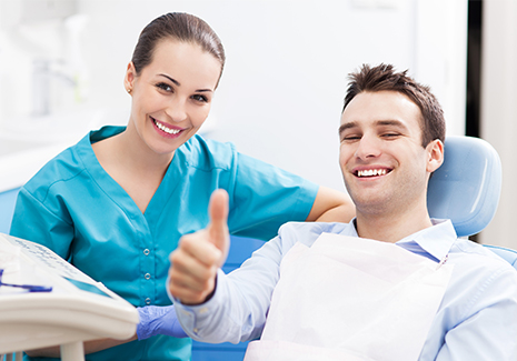 Patient and dentist smiling and giving thumbs up