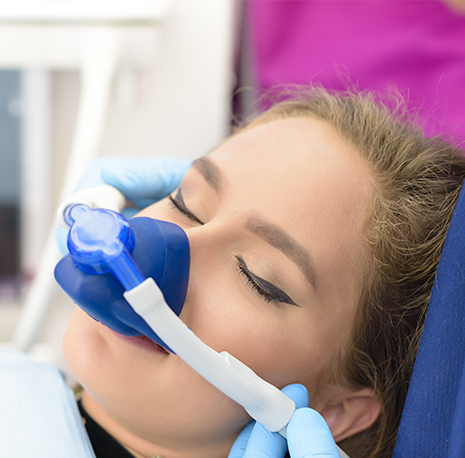 A young woman under inhalation sedation in dentist chair